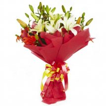 White lilies bouquet with red paper wrapping
