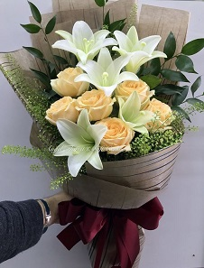 4 White Lilies with 6 peach roses in a bouquet wrapped in brown