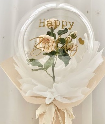 A bouquet of single clear balloon with happy birthday printed wrapped in white and jute with one white rose inside the balloon