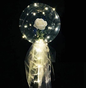 Single white rose in a clear balloon wrapped in white